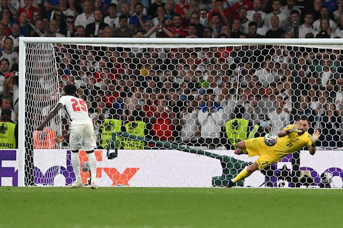 Bukayo Saka of England misses his team's fifth penalty in a shootout which is saved by Gianluigi Donnarumma of Italy during the UEFA Euro 2020 Championship Final between Italy and England at Wembley Stadium in London on July 11, 2021. / Credit: Paul Ellis/ Getty Images