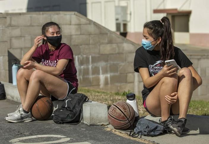 MONTEREY PARK, CA - MARCH 26, 2021: Kendall Tam, left, a senior at Mark Keppel High School and captain of the girls varsity basketball team, talks with Emily Liu, a junior, before start of a practice session at the school in Monterey Park. This was the first week back to practice since a year ago last March when everything came to a halt due to the coronavirus outbreak. (Mel Melcon / Los Angeles Times)