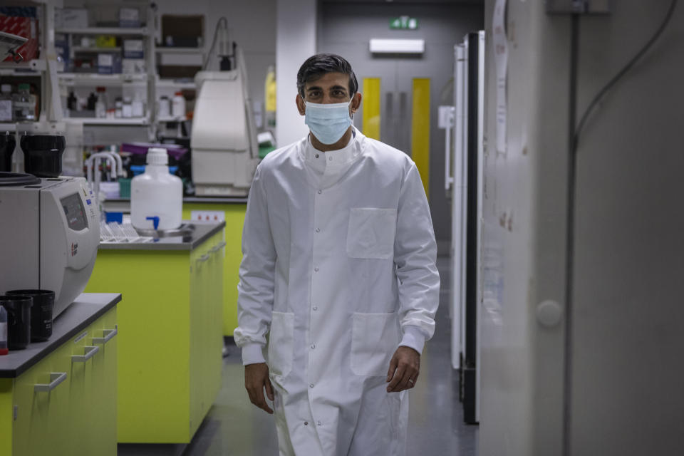 Britian's Chancellor of the Exchequer Rishi Sunak walks, during a visit to Imperial Clinic Research Facility at Hammersmith Hospital, where he met staff and was instructed on research techniques, to mark the announcement of his Spending Review, in London, Wednesday, Nov. 25, 2020. (Jack Hill/Pool Photo via AP)