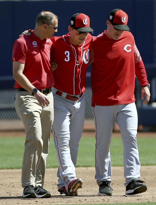 Cincinnati Reds second baseman Scooter Gennett (3) leaves the baseball game with the help of manager David Bell, right, and head athletic trainer Steve Baumann, left, after he was injured in the second inning of a spring training baseball game against the Milwaukee Brewers, Friday, March 22, 2019, in Phoenix. (AP Photo/Ross D. Franklin)