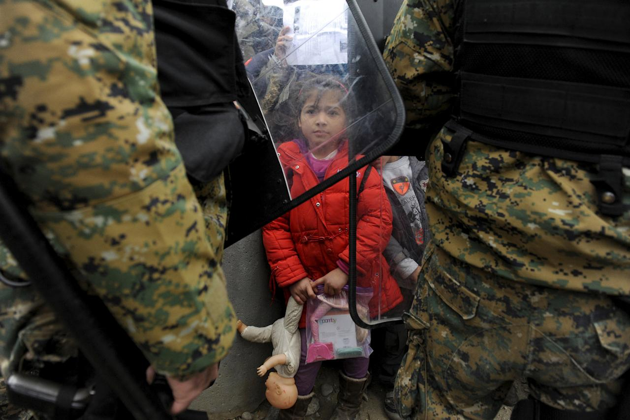 A migrant girl holds her toys as Macedonian policemen block migrants at the Greek-Macedonian borders, near the village of Idomeni, Greece November 20, 2015. Balkan countries have begun filtering the flow of migrants to Europe, granting passage to those fleeing conflict in the Middle East and Afghanistan but turning back others from Africa and Asia, the United Nations and Reuters witnesses said on Thursday.  REUTERS/Alexandros Avramidis      TPX IMAGES OF THE DAY