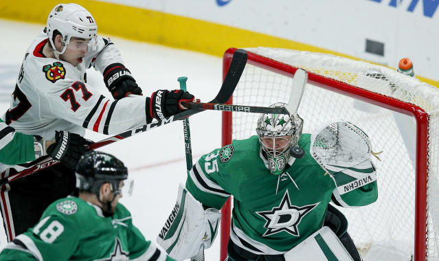 Chicago Blackhawks forward Kirby Dach (77) attempts to deflect a shot past Dallas Stars goaltender Anton Khudobin (35) during the third period of an NHL hockey game, Sunday, Feb. 23, 2020, in Dallas. Dallas won 2-1. (AP Photo/Brandon Wade)