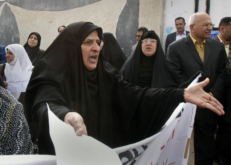 An Iraqi woman reacts while protesters chant slogans during a protest in Basra, Iraq's second-largest city, 550 kilometers (340 miles) southeast of Baghdad, Iraq, Wednesday, March 16, 2011. More than 200 employees of Basra customs directorate took part in a protest in front of Basra customs building, demanding the dismissal of the director general of Basra customs because they claimed he is a military man and has no experience in customs affairs. (AP Photo/Nabil al-Jurani)