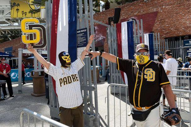 PHOTO: Baseball fans Mercury Hornbeek and Steven Ames wait in line before the gates opened up before a baseball game between the Arizona Diamondbacks and the San Diego Padres in San Diego, April 1, 2021. (Denis Poroy/AP)