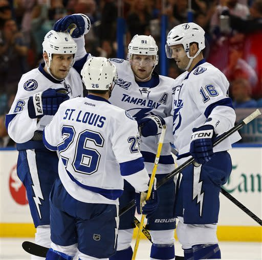 Tampa Bay Lightning's Steven Stamkos (91) celebrates his second-period goal with teammates, from left, Sami Salo, of Sweden, Martin St. Louis, and Teddy Purcell during an NHL hockey game against the Carolina Hurricanes, Sunday, April 21, 2013, in Tampa, Fla. (AP Photo/Mike Carlson)