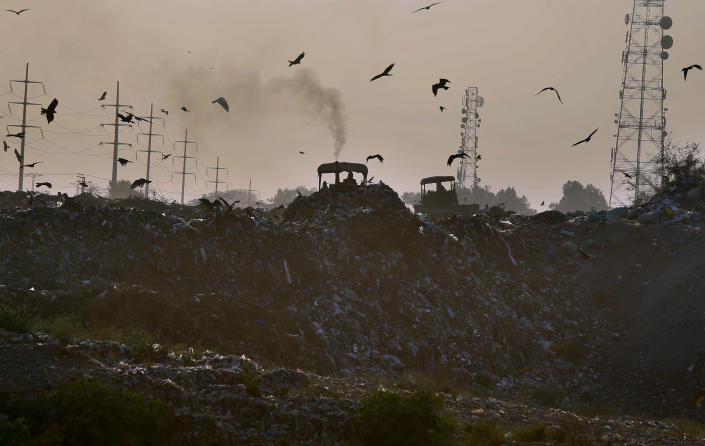 Smoke is emitted from the silencer of a tractor working on a garbage-dump on the outskirts of Islamabad, Pakistan, Tuesday, Dec. 4, 2018. The COP 24 UN Climate Change Conference is taking place in Katowice, Poland where negotiators from around the world are meeting for talks on curbing climate change. (AP Photo/Anjum Naveed)