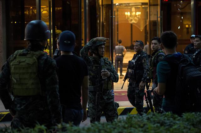 <p>Philippines' police officers gesture as they stand guard by the Resorts World Hotel in Manila on June 2, 2017 following an assault. (Photo: Noel Celis/AFP/Getty Images) </p>