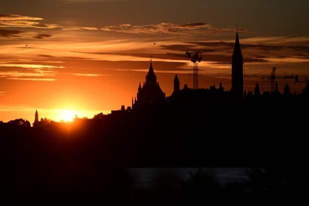 An annular solar eclipse rises behind Parliament Hill in Ottawa on June 10, 2021. By the time the sun rises on Friday, Ottawa and the rest of the province will be under new pandemic rules. (Sean Kilpatrick/Canadian Press - image credit)