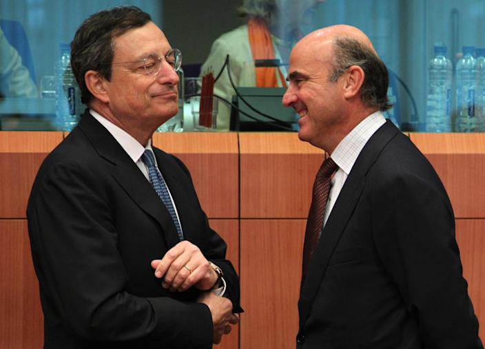 Spanish Finance Minister Luis de Guindos Jurado, right, talks with President of the European Central Bank Mario Draghi during the Eurogroup ministerial meeting at the European Council building in Brussels, Monday, July 9, 2012. European finance ministers are to use this week's meetings in Brussels to attempt to secure Spain's teetering economy, with progress expected on the bailout loan for the country's stricken banks and a relaxation of the government's financial targets. (AP Photo/Yves Logghe)