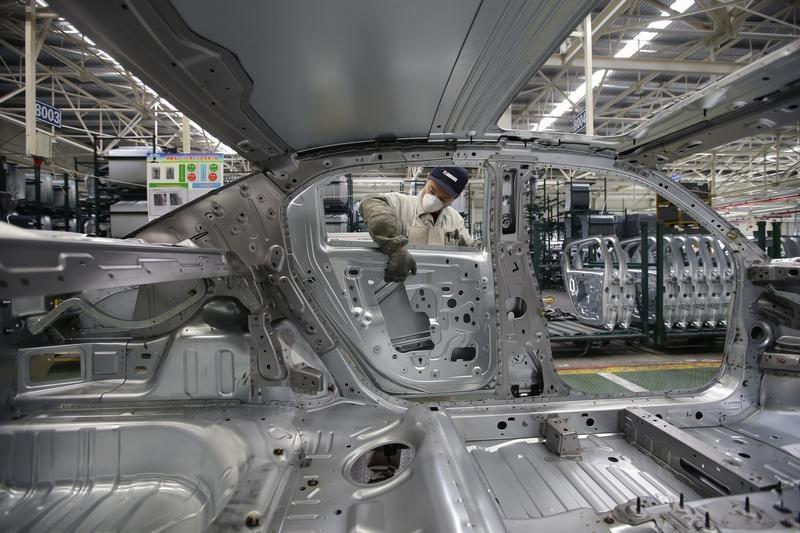 An employee installs car doors at a production line of Dongfeng Peugeot Citroen Automobile factory in Wuhan