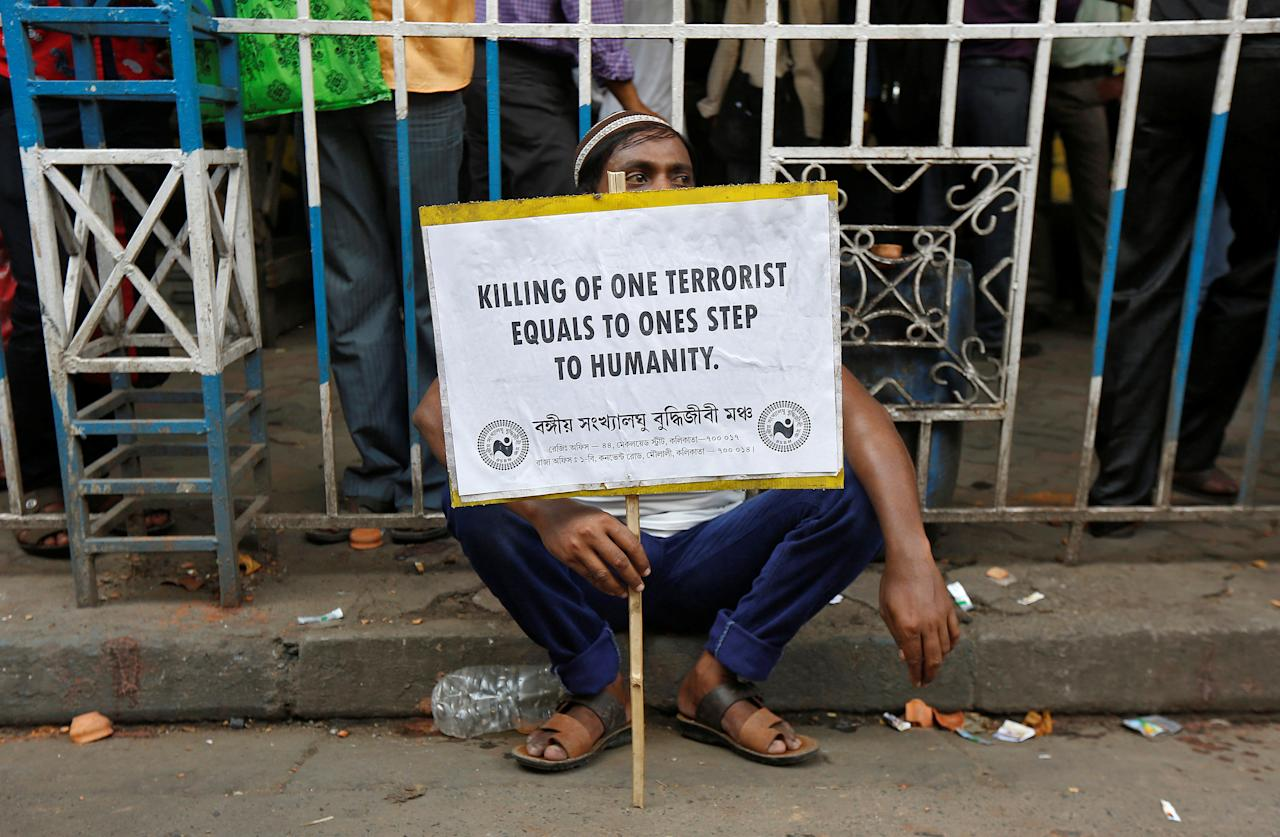 A demonstrator carrying a placard sits on a pavement as he waits to participate in a protest organised by a Muslim minority forum against terrorism in Kolkata, India, July 28, 2016. REUTERS/Rupak De Chowdhuri