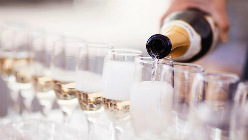 Champagne poured into a row of flutes