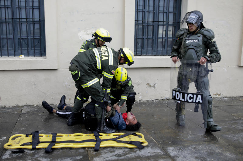 Police attend an anti-government protester affected by tear gas during clashes in downtown Bogota, Colombia, Friday, Nov. 22, 2019. Labor unions and student leaders called on Colombians to bang pots and pans Friday evening in another act of protest while authorities announced three people had died in overnight clashes with police after demonstrations during a nationwide strike. (AP Photo/Ivan Valencia)
