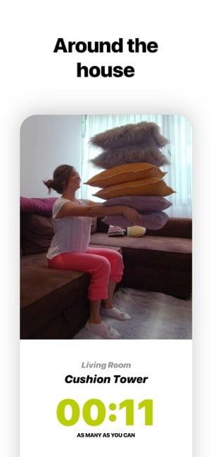 Screenshot of Wakeout app showing a woman exercising by lifting a stack of cushions and text saying Around the house