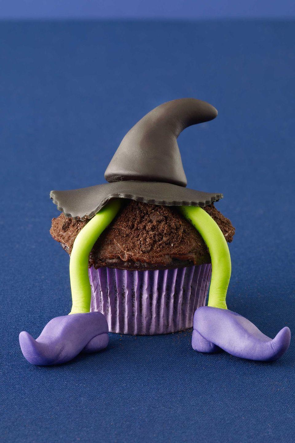 """<p>A fondant Wicked Witch of the East-like figure dangles deliciously from her perch: a cupcake topped with chocolate frosting and a dusting of crushed chocolate wafer cookies.</p><p><a href=""""https://www.womansday.com/food-recipes/food-drinks/recipes/a11480/wicked-witch-cupcake-recipe-122724/"""" rel=""""nofollow noopener"""" target=""""_blank"""" data-ylk=""""slk:Get the Wicked Witch Cupcake recipe."""" class=""""link rapid-noclick-resp""""><em>Get the Wicked Witch Cupcake recipe.</em></a></p>"""