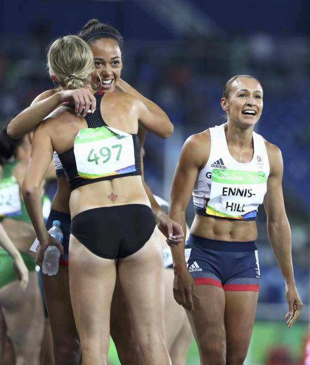 2016 Rio Olympics - Athletics - Women's Heptathlon 800m - Olympic Stadium - Rio de Janeiro, Brazil - 13/08/2016. Brianne Theisen-Eaton (CAN) of Canada (497) hugs Katarina Johnson-Thompson (GBR) of Britain, next to Jessica Ennis-Hill (GBR) of Britain (R). REUTERS/Lucy Nicholson FOR EDITORIAL USE ONLY. NOT FOR SALE FOR MARKETING OR ADVERTISING CAMPAIGNS.