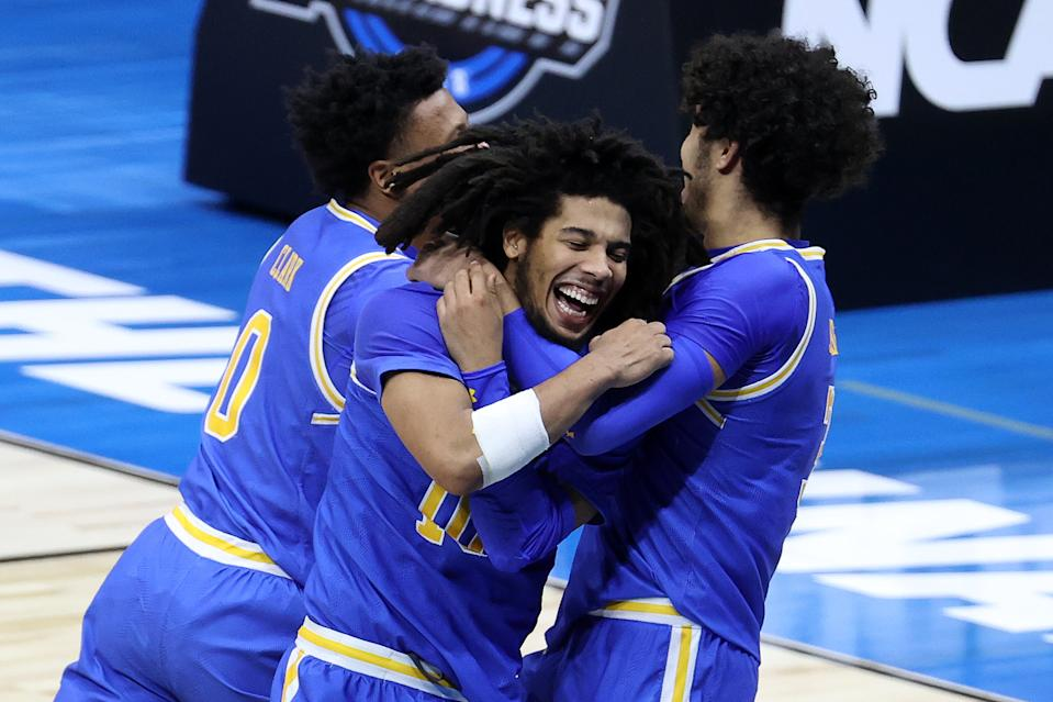 INDIANAPOLIS, INDIANA - MARCH 30: Tyger Campbell #10 and Johnny Juzang #3 of the UCLA Bruins celebrate defeating the Michigan Wolverines 51-49 in the Elite Eight round game of the 2021 NCAA Men's Basketball Tournament at Lucas Oil Stadium on March 30, 2021 in Indianapolis, Indiana. (Photo by Andy Lyons/Getty Images)