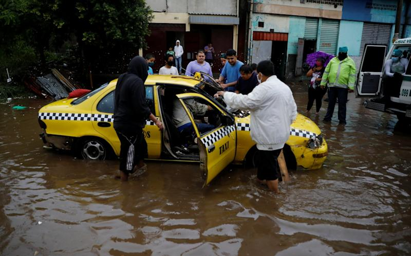People try to move a taxi dragged by the water during floods caused by Tropical Storm Amanda at El Modelo neighborhood, in San Salvador (REUTERS)