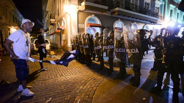 PHOTO: Demonstrators stand in front of riot control units during clashes in San Juan, Puerto Rico, Monday, July 22, 2019. Protesters are demanding Gov. Ricardo Rossello step down following the leak of an offensive, obscenity-laden online chat. (AP Photo/Carlos Giusti)