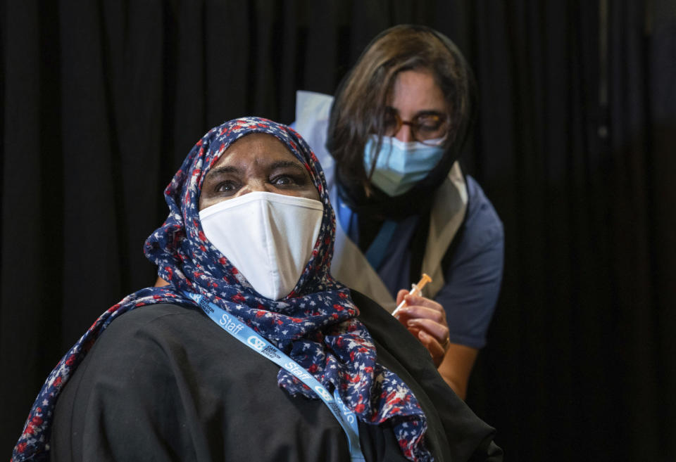 A woman, name not given, is vaccinated at a Covid-19 pop-up vaccination centre, at the East London Mosque in Whitechapel, London, Saturday Feb. 6, 2021. Britain's vaccination program is pushing to offer a vaccination to aged, vulnerable and care workers by mid-February. (Dominic Lipinski/PA via AP)