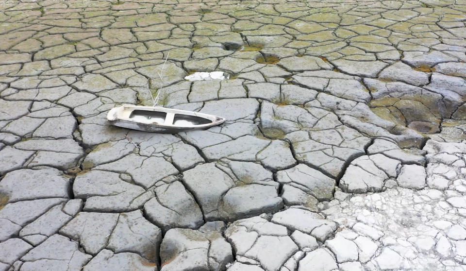 In this photo released by Nantou County Government, a boat is stranded on a dried lakebed in Sun Moon Lake in Nantou county in central Taiwan on April 23, 2021. Some households in Taiwan are going without running water two days a week after a months-long drought dried up the island's reservoirs and a popular tourist lake. (Nantou County Government via AP)