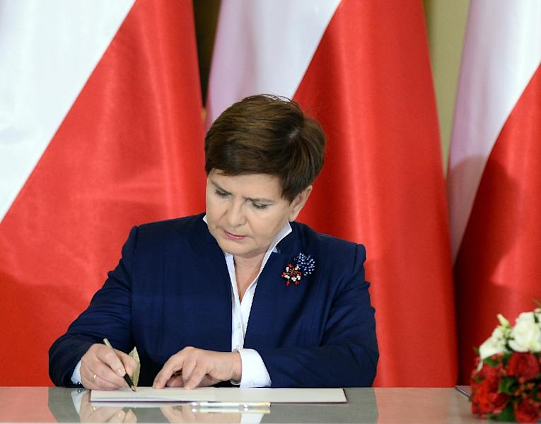 Beata Szydlo signs her letter of appointment as she is sworn in as new Polish Prime Minister at the Presidential Palace in Warsaw on November 16, 2015 (AFP Photo/Janek Skarzynski)