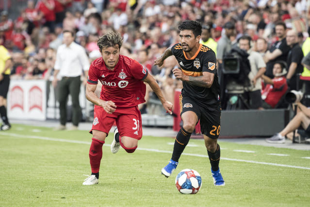 Toronto FC forward Tsubasa Endoh (31) chases down Houston Dynamo defender A. J. DeLaGarza (20) during the first half of an MLS soccer game, Saturday, July 20, 2019 in Toronto. (Christopher Katsarov/The Canadian Press via AP)