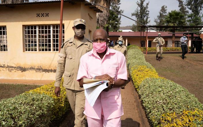 Paul Rusesabagina (R) in the pink inmate's uniform arrives from the Nyarugenge prison at the Nyarugenge Court of Justice in Kigali - SIMON WOHLFAHRT /AFP