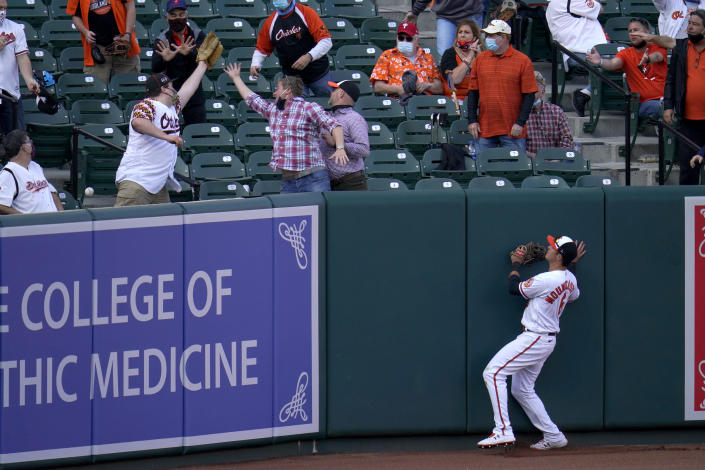 Baltimore Orioles left fielder Ryan Mountcastle looks on as a ball goes over the wall on a solo home run by Boston Red Sox's Enrique Hernandez during the eighth inning of a baseball game, Thursday, April 8, 2021, on Opening Day in Baltimore. The Red Sox won 7-3. (AP Photo/Julio Cortez)