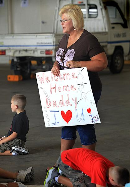 Cindy Jendrusch holds a finished poster made by her grandson for his father, Gunnery Sgt. Josh Miller, during a banner-making party at a hangar at New River Air Station near Camp Lejeune in Jacksonville, N.C. Families and friends will hang large sheets and banners on a fence outside the base to welcome home Marines from Afghanistan and Iraq, and wave posterboard signs as they wait for their arrival. (AP Photo/Chuck Beckley)