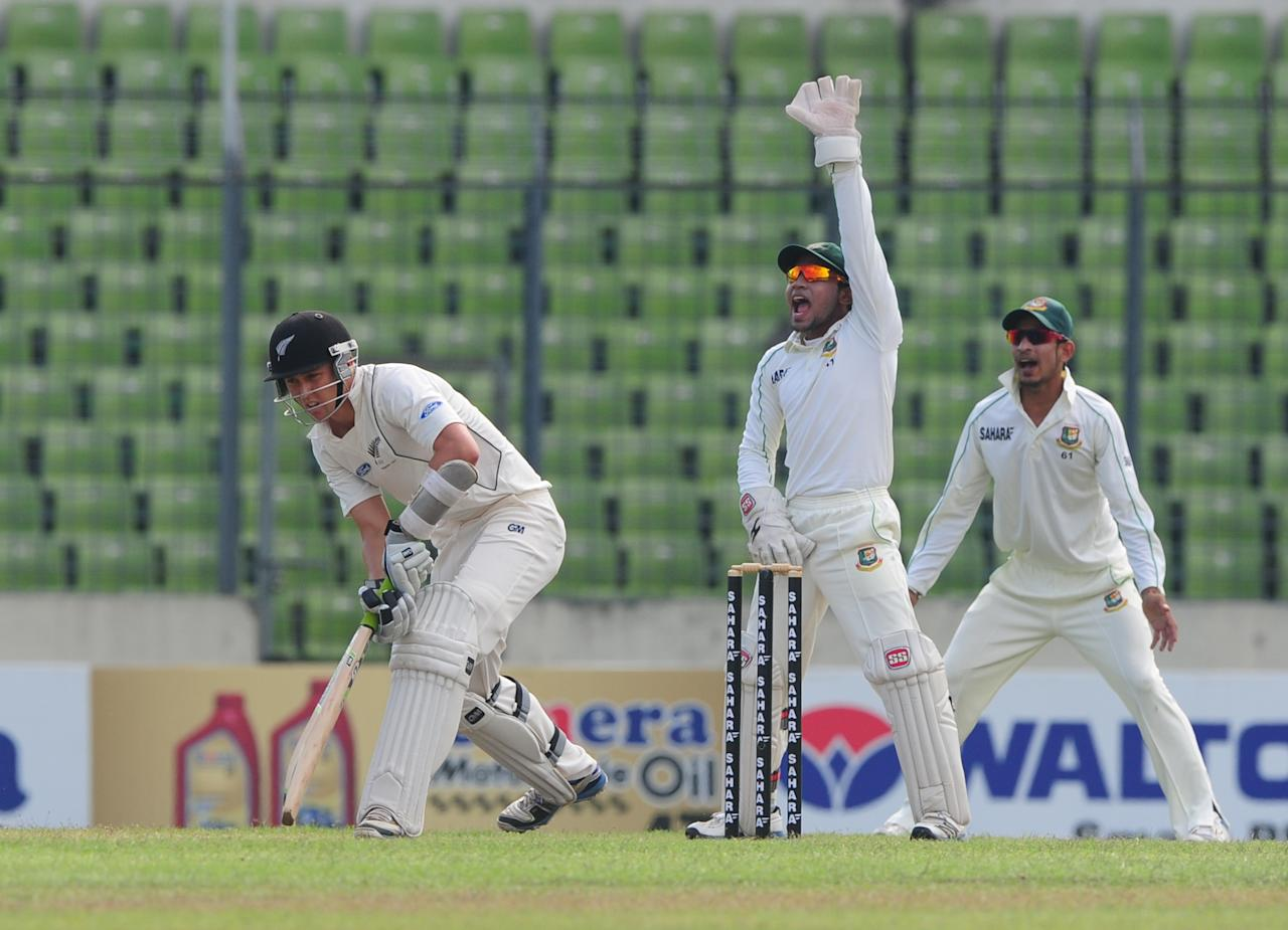 Bangladesh cricket captain Mushfiqur Rahim (C) apeals for an LBW before a successful decision against New Zealand batsman Trent Boult (L) as the Bangladesh cricketer Nasir Hossain (R) looks on during the fourth day of the second cricket Test match between Bangladesh and New Zealand at the Sher-e Bangla National Stadium in Dhaka on October 24, 2013. AFP PHOTO/ Munir uz ZAMAN        (Photo credit should read MUNIR UZ ZAMAN/AFP/Getty Images)