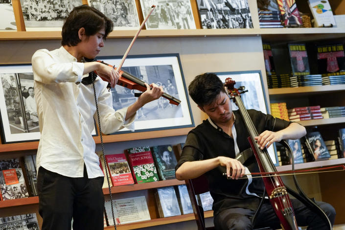 """ARKAI band members Jonathan Miron, left, and Philip Sheegog play """"In Radiance"""" during the press preview of """"Responses: Asian American Voices Resisting the Tides of Racism"""" at the Museum of Chinese in America, Wednesday, July 14, 2021, in New York. (AP Photo/Mary Altaffer)"""