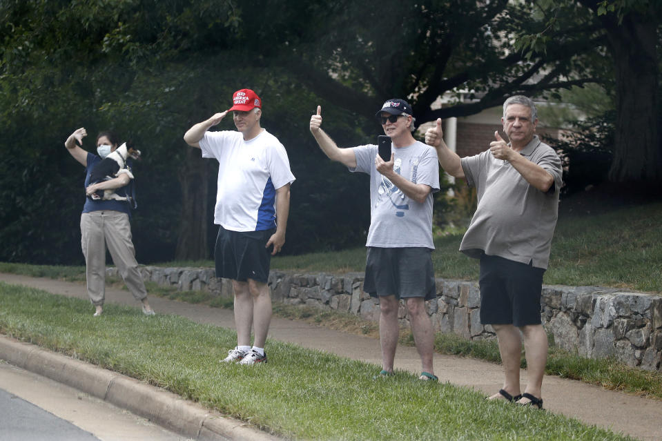 People watch the motorcade for President Donald Trump drive to Trump National Golf Club in Sterling, Va., Saturday, July 11, 2020. (AP Photo/Patrick Semansky)