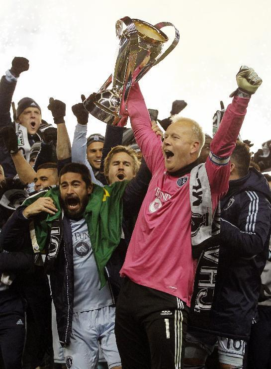 Sporting Kansas City's Paulo Nagamura, front left, and goalkeeper Jimmy Nielsen, front right, hold the MLS Cup as they celebrate their 2-1 win over Real Salt Lake in the MLS Cup soccer final match in Kansas City, Kan., Saturday, Dec. 7, 2013. (AP Photo/Colin E. Braley)