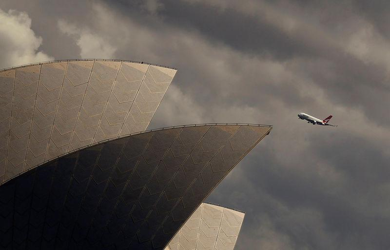 FILE PHOTO - A Qantas A-380 plane flies past the Sydney Opera house in central Sydney