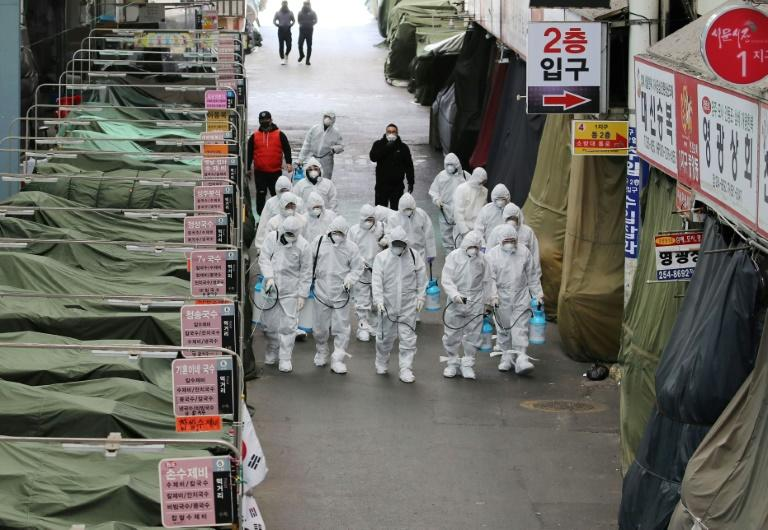 Workers in protective gear spray disinfectant at a market in the southeastern city of Daegu