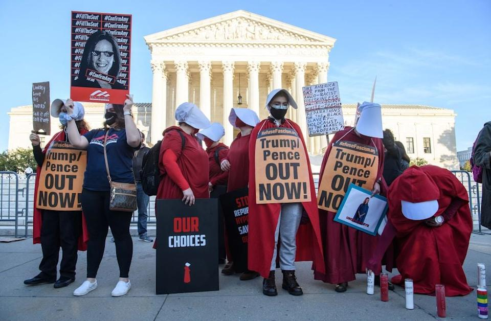 <p>Protesters dressed in 'The Handmaid's Tale'-inspired costumes demonstrate outside the US Supreme Court on Capitol Hill in October, 2020</p> (AFP via Getty Images)