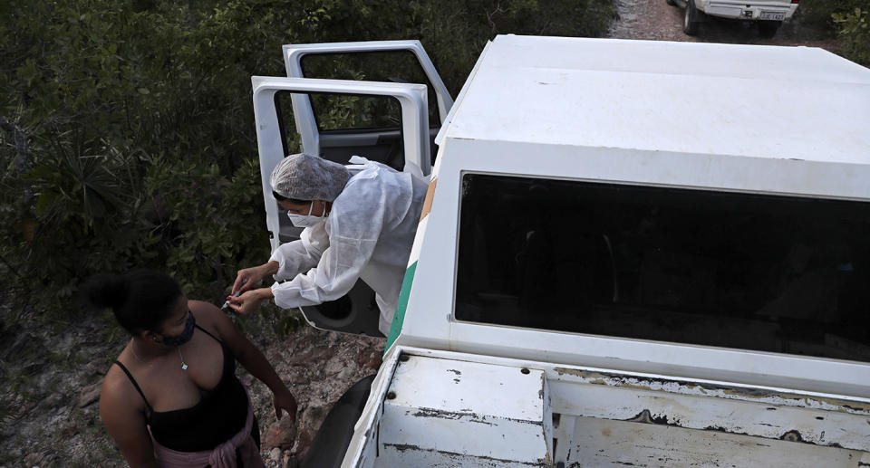 A health worker leans out of a vehicle to give a woman a vaccine.