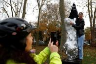 A person takes a photo as a protester covers with a t-shirt the Mary Wollstonecraft statue 'Mother of feminism' by artist Maggi Hambling in Newington Green, London