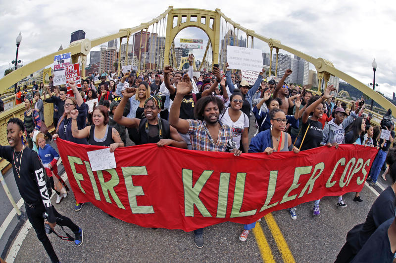 FILE – In this June 22, 2018, file photo, demonstrators protesting the fatal police shooting of Antwon Rose Jr. cross the Roberto Clemente Bridge during an evening rush hour march that began in downtown Pittsburgh. The fatal police shooting of Rose as he fled during a traffic stop on June 19, is the first in the Pittsburgh area in the Black Lives Matter era, and it is galvanizing residents who say they've been frustrated for too long. (AP Photo/Gene J. Puskar, File)