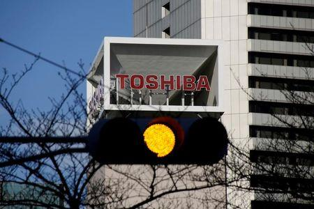 FILE PHOTO: Logo of Toshiba Corp is seen behind a traffic signal at its headquarters in Tokyo