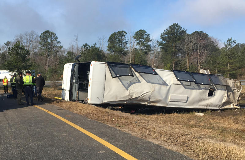 This photo provided by Virginia State Police emergency responders at the scene after a charter bus overturned on an Interstate 95 exit near Kingwood, Va., Tuesday, March 19, 2019. Virginia State Police say in a statement that the Tao's Travel Inc. bus with 57 people aboard overturned on an Interstate 95 exit Tuesday in Prince George County. Police say that as the bus turned onto the exit, it ran off the left side and overturned. (Virginia State Police via AP)
