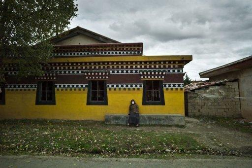 A woman sits against a wall of the Kirti monastary in the town of Aba, in China's Sichuan province, on October 17. Tibetan Buddhist monks in China say a wave of self-immolations is linked to Beijing's refusal to engage with the Dalai Lama, and fear the protests will make their lives even more difficult