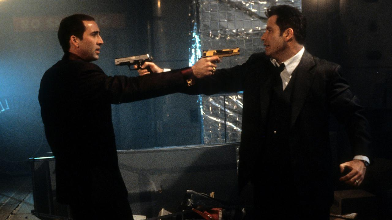 Nicolas Cage and John Travolta aiming guns at each other in a scene from the film 'Face/Off,' 1997.  - Touchstone/Getty