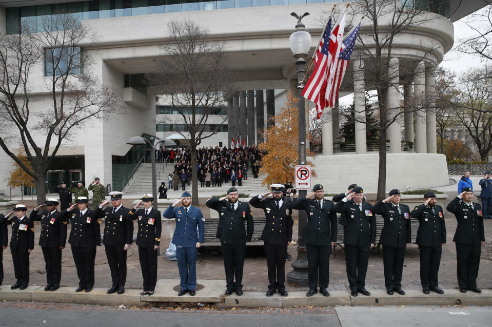 Canadian military salute on the sidewalk outside the Canadian Embassy, as the hearse carrying the flag-draped casket of former President George H.W. Bush drive by on Pennsylvania Ave. from the Capitol to a State Funeral at the Washington National Cathedral on December 5, 2018 in Washington, DC. (Photo: Alex Brandon – Pool/Getty Images)