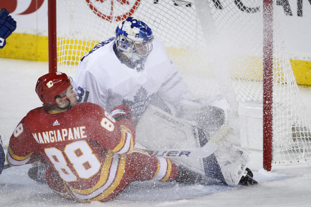Toronto Maple Leafs goalie Frederik Andersen, right, is sprayed with ice by Calgary Flames' Andrew Mangiapane during the second period of an NHL hockey game, Thursday, Dec. 12, 2019 in Calgary, Alberta. (Jeff McIntosh/The Canadian Press via AP)