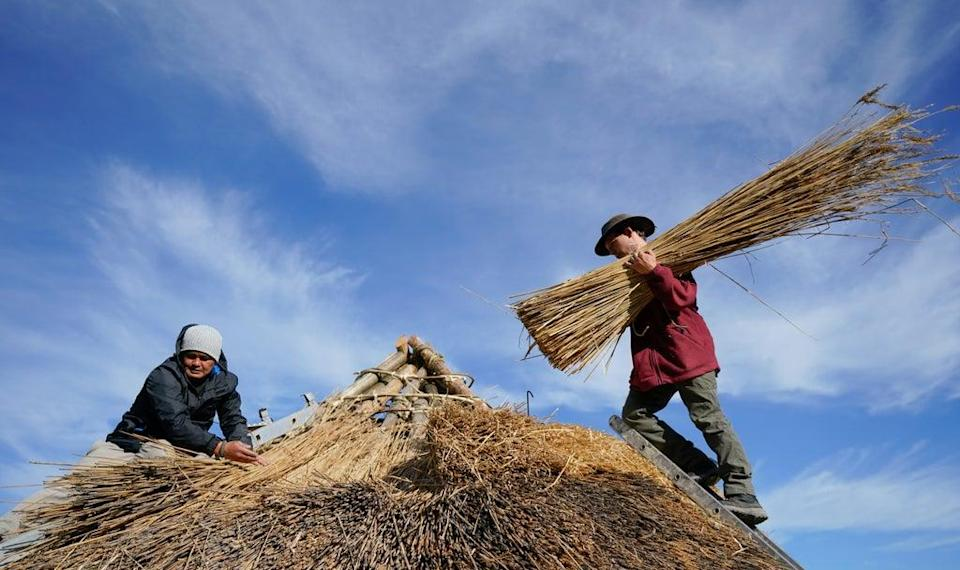 Veteran Jesse Swanson (left) joins Butser Ancient Farm's Will Scanlan as they thatch the roof (Andrew Matthews/PA) (PA Wire)