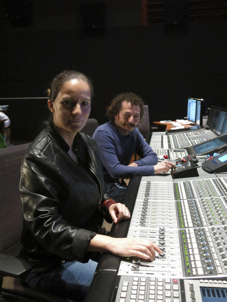 """Mexican sound engineers Michelle Couttolenc, left, and Jaime Baksht pose in a sound studio in Mexico City, March 18, 2021. The Oscar-nominated movie """"Sound of Metal,"""" about a heavy metal drummer that starts going deaf, has three Mexican sound engineers nominated for best sound, Couttolenc and Baksht. (AP Photo/Berenice Bautista)"""