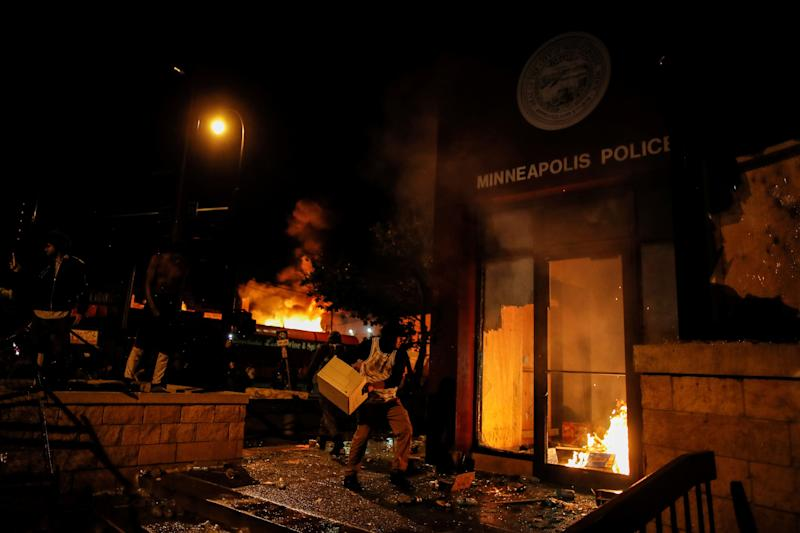 A protester sets fire to the entrance of a police station in Minneapolis. REUTERS/Carlos Barria (Photo: Carlos Barria / Reuters)