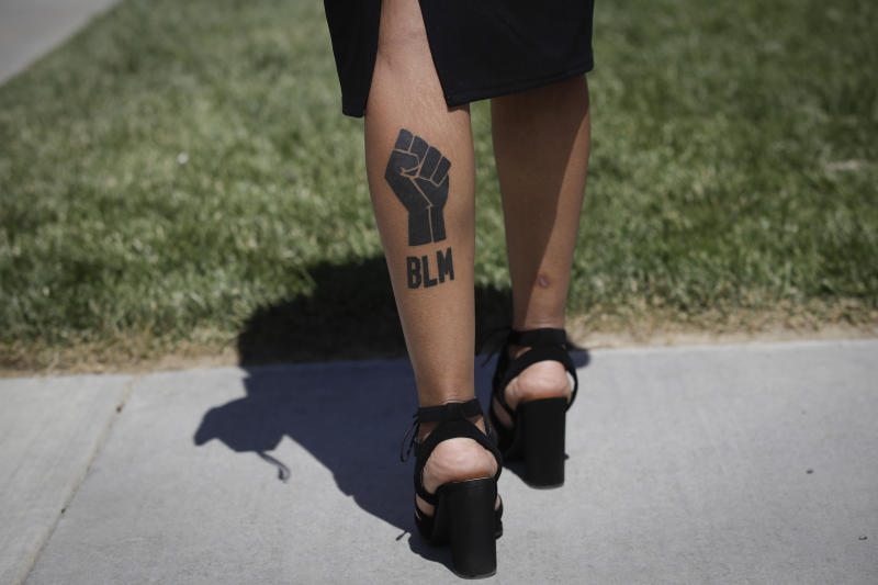 Shaneeze Flax has a Black Lives Matter tattoo on her calf as she attends a funeral for Robert Fuller on Tuesday, June 30, 2020, in Littlerock, Calif. Fuller, a 24-year-old Black man, was found hanging from a tree in a park in a Southern California high desert city. Authorities initially said the death of Fuller appeared to be a suicide but protests led to further investigation, which continues. (AP Photo/Marcio Jose Sanchez)